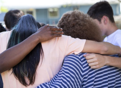 A group of teens with their arms around one another.